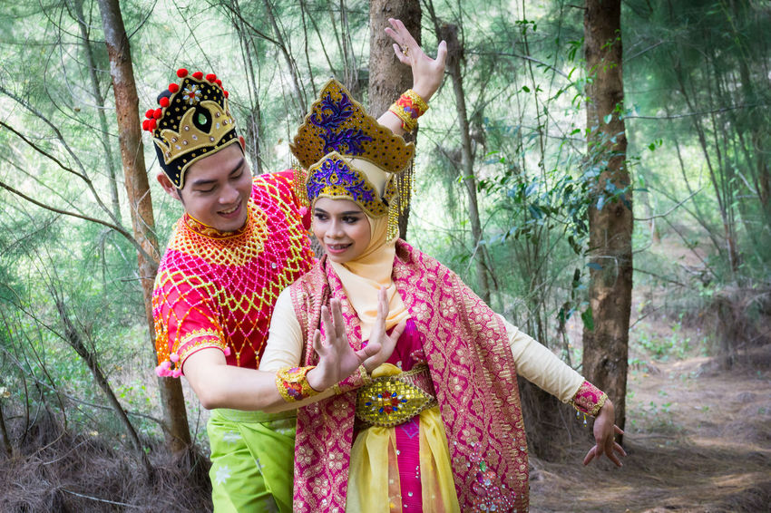 Specific to the villages of Kelantan, where the tradition originated, Mak Yong is performed mainly as entertainment or ritual purposes by couple of dancers. Adult Crown Day Forest Friendship Happiness Headdress Headwear Lifestyles Mak Yong Outdoors People Real People Smiling Togetherness Traditional Clothing Tree Two People Young Adult Young Women