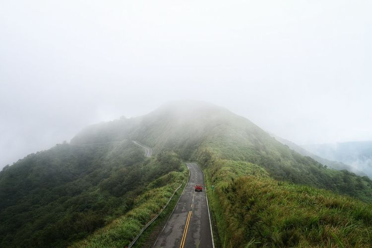 Car On Road Leading Towards Mountain Against Sky During Foggy Weather