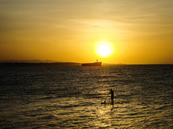 Scenic View Of Person Paddleboarding At Sunset