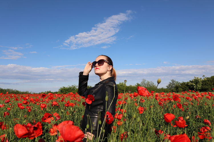 Young woman standing by poppy flowers on field against sky