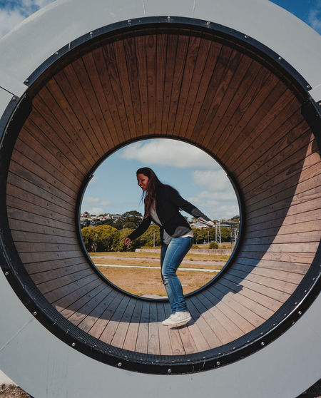 Full length of woman standing on circular structure