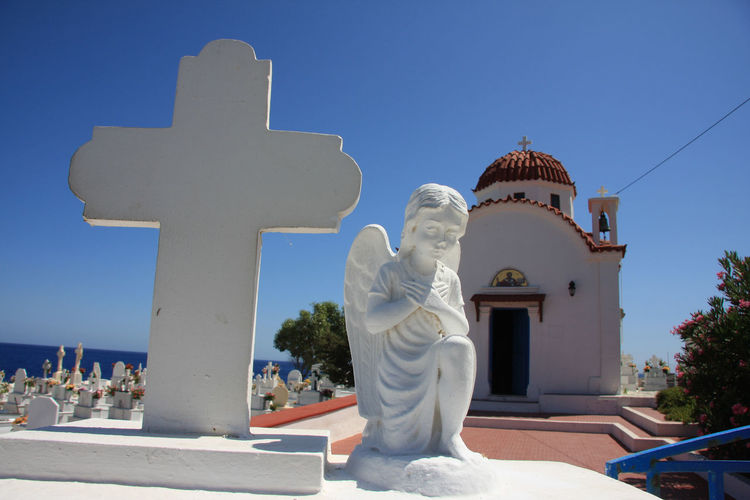 Angel statue and cross outside church against clear blue sky at karpathos