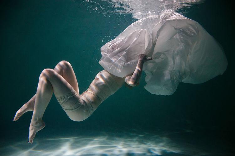 Woman sinking in swimming pool