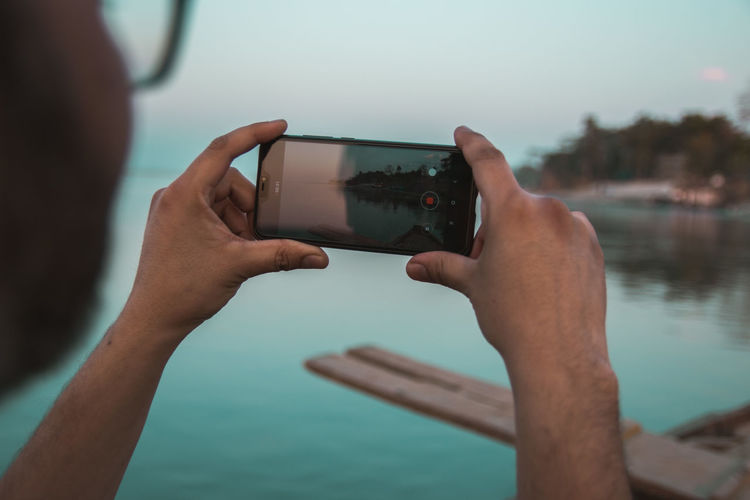 Cropped hands of man photographing lake with smart phone