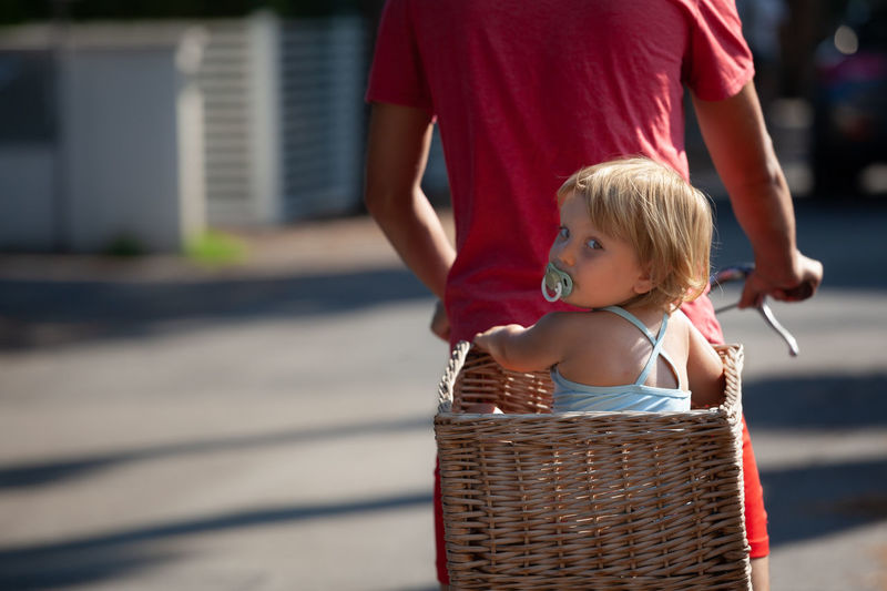 Midsection of father with daughter in wicker basket riding bicycle on street