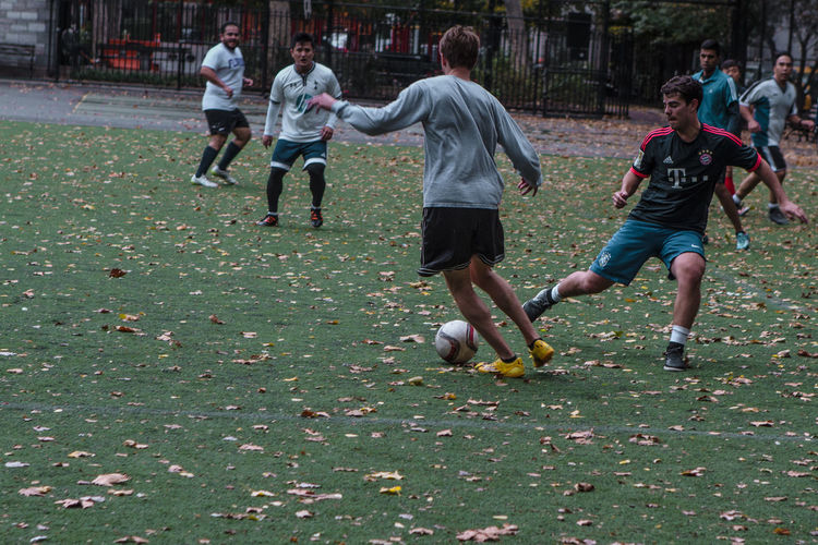 Group of people playing soccer on field