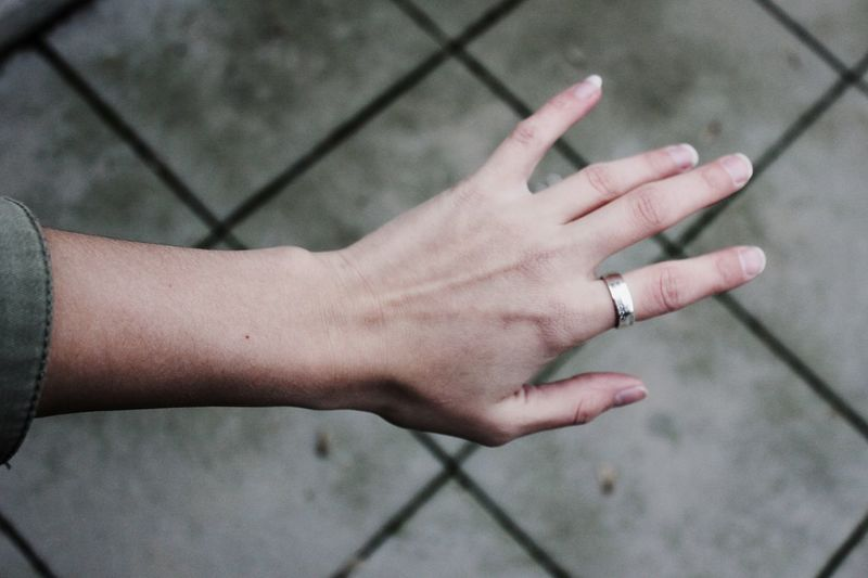 Cropped hand of woman wearing ring over footpath