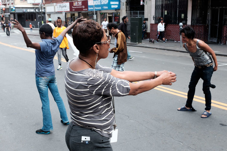 Rear view of woman photographing in city