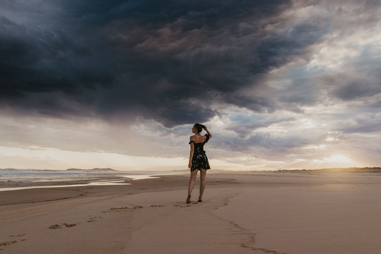 Sky Land One Person Beach Cloud - Sky Full Length Standing Sea Leisure Activity Water Beauty In Nature Nature Sand Scenics - Nature Adult Real People Casual Clothing Lifestyles Horizon Over Water Outdoors Dune Desert Sunset Woman Storm Cloud
