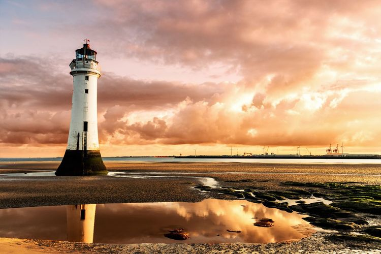 Lighthouse At Beach Against Cloudy Sky During Sunset