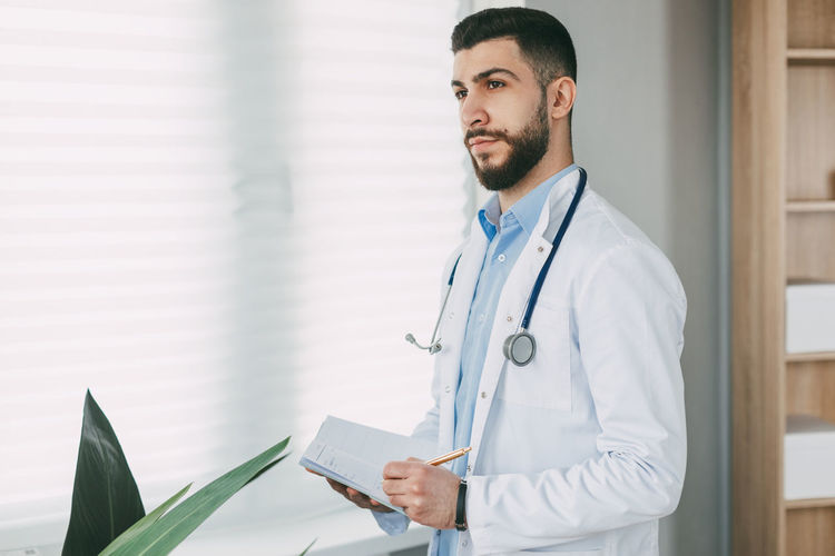 Modern young male doctor stands in his office and writes in his notebook