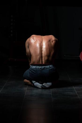 Rear view of shirtless man sitting on floor