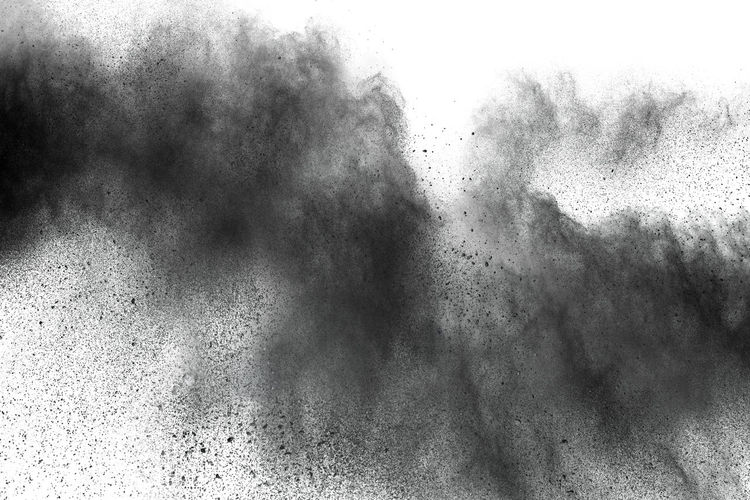Defocused image of black powder paints against white background