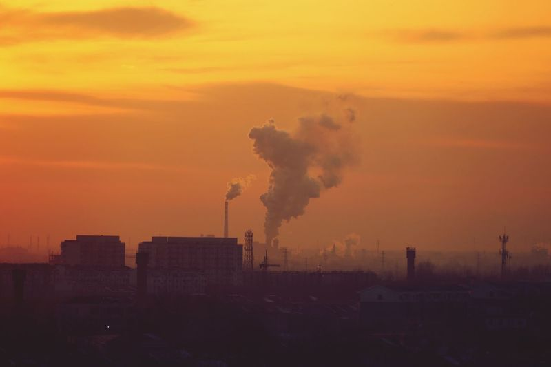Smoke Emitting From Factories Against Sky During Sunset