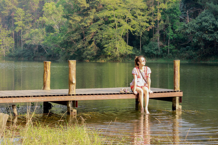 Woman Sitting On Pier In Lake Against Trees