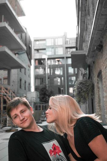 Portrait of friends against buildings in city