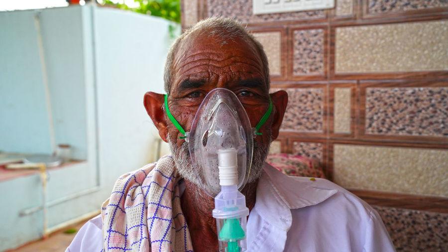 Close-up portrait of senior wearing oxygen mask