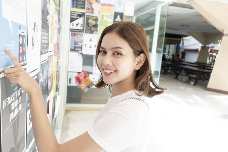 Portrait of smiling woman pointing over document on bulletin board in corridor