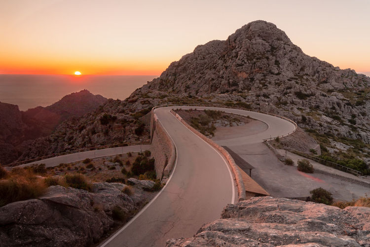 Road leading towards mountains against sky during sunset