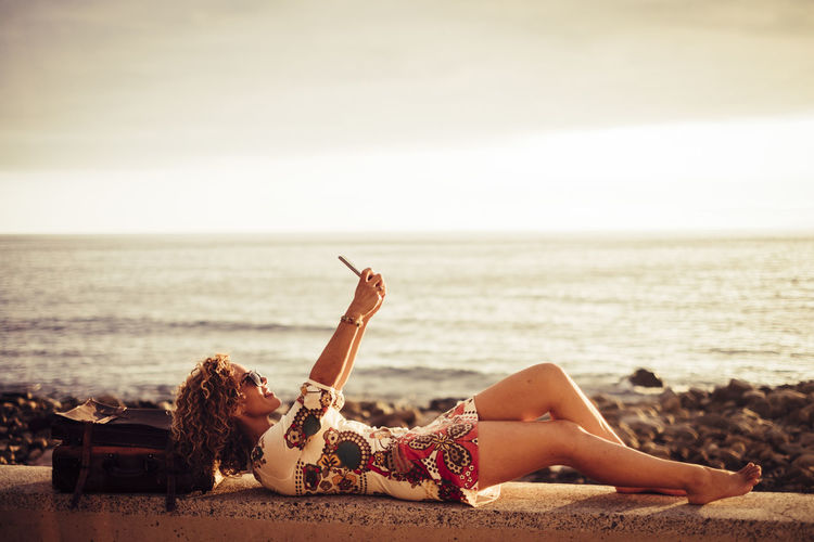 Side view of woman taking selfie while lying on retaining wall at beach against sky during sunset