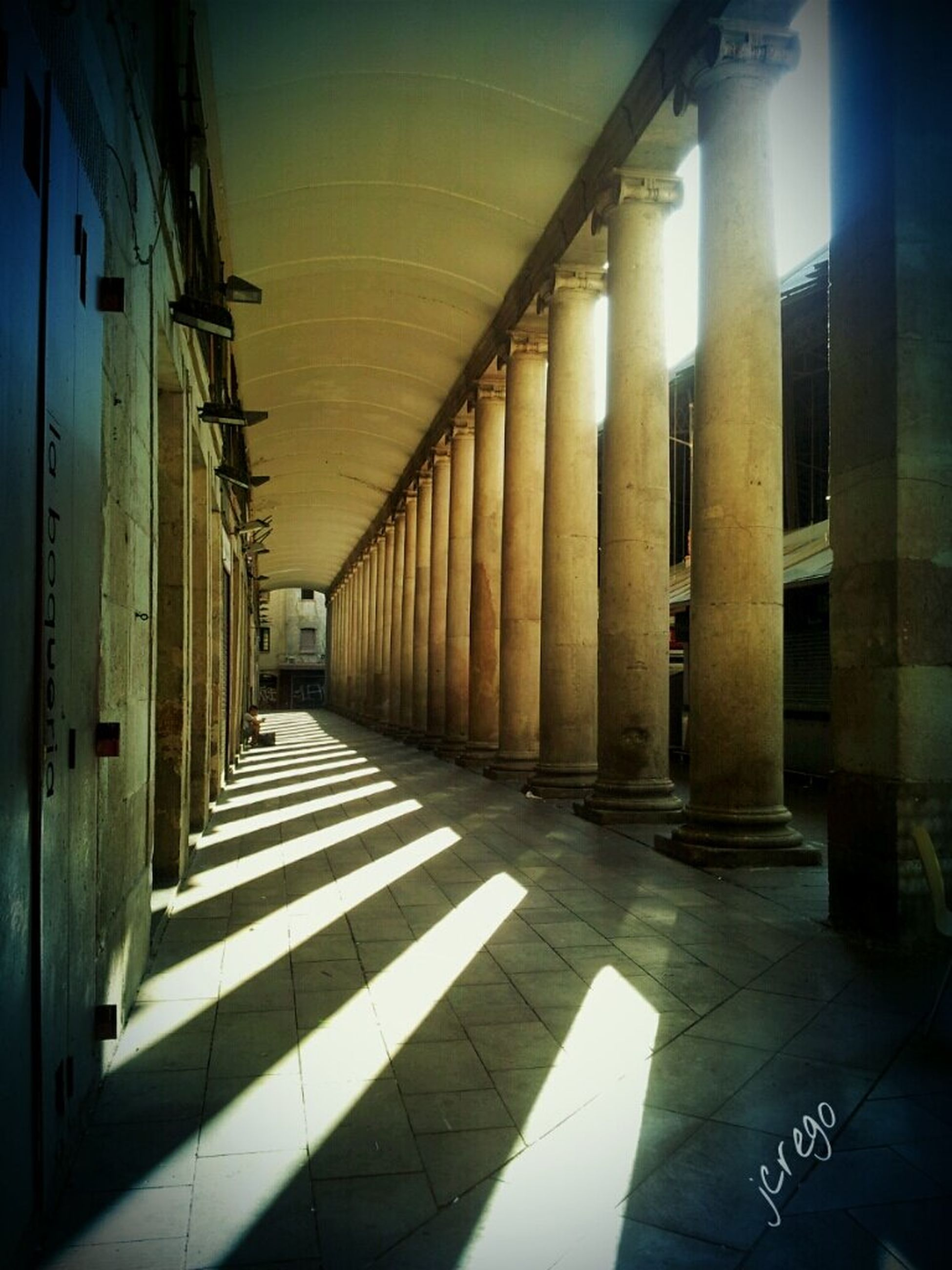 indoors, corridor, architecture, the way forward, built structure, architectural column, diminishing perspective, column, flooring, empty, in a row, colonnade, tiled floor, building, narrow, ceiling, sunlight, absence, vanishing point, shadow