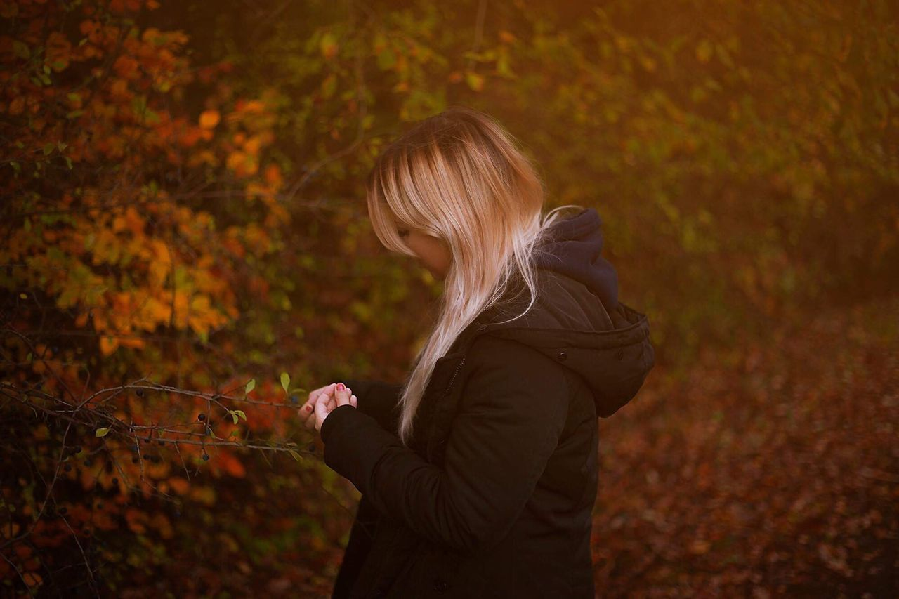 real people, one person, lifestyles, waist up, land, leisure activity, hairstyle, autumn, hair, side view, holding, casual clothing, change, nature, tree, long hair, young adult, three quarter length, blond hair, plant, outdoors, warm clothing