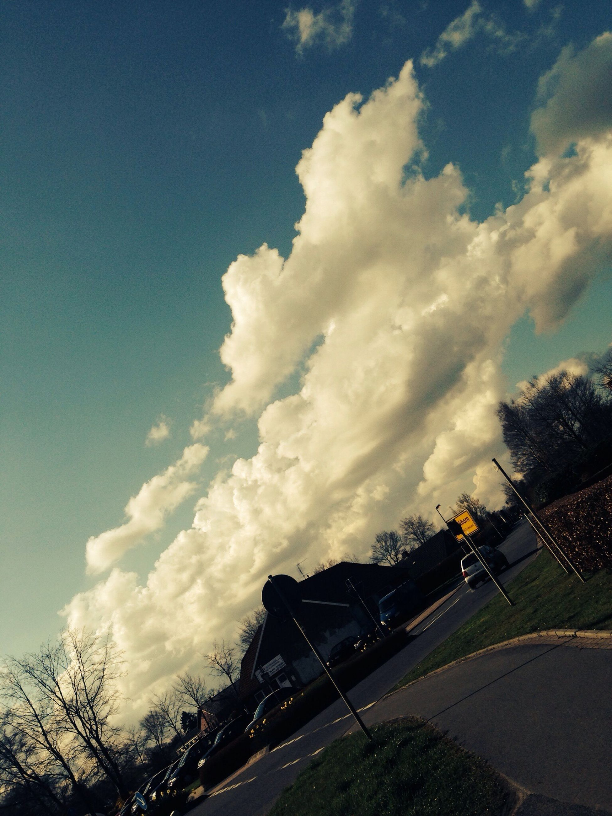 sky, cloud - sky, built structure, transportation, architecture, tree, road, land vehicle, cloud, building exterior, dusk, cloudy, low angle view, outdoors, car, mode of transport, nature, connection, no people, street