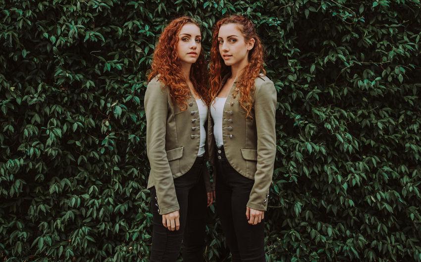 Portrait of siblings standing against plants