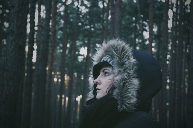 Side view of young woman wearing fur hood against trees at forest