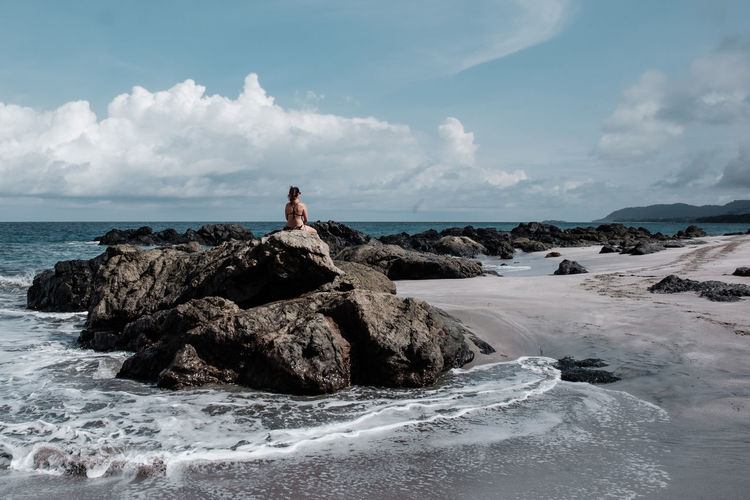 Rear view of woman sitting on rocky shore against sky