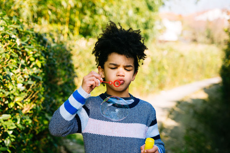 Afro Fun Happy Little Boy Afrohair Blowing Bubbles Casual Clothing Child Childhood Front View Kid Nature One Person Outdoors Playful Playing Sunny Day Waist Up