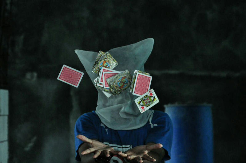 Obscured face of man playing cards