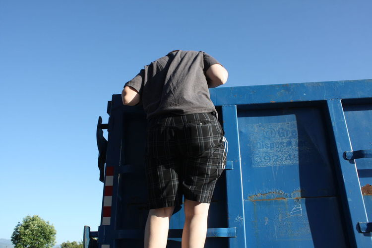 Low angle view of man on dumpster