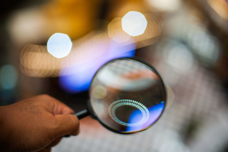 Man Holding Magnifying Glass In Front Of Glowing Circle