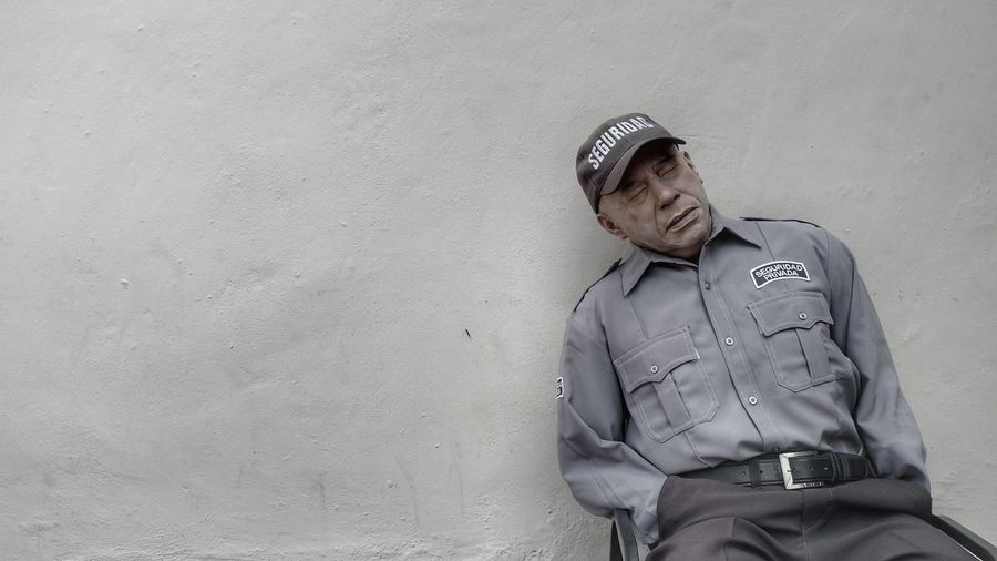Security Guard Sleeping Against Wall