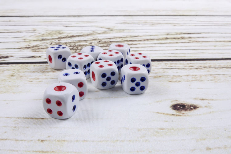 DICES ON A WOODEN TABLE Arts Culture And Entertainment Close-up Dice Gambling Game Of Chance Group Of Objects Leisure Activity Leisure Games Luck No People Number Opportunity Red Relaxation Sport Spotted Still Life Table White Color Wood - Material