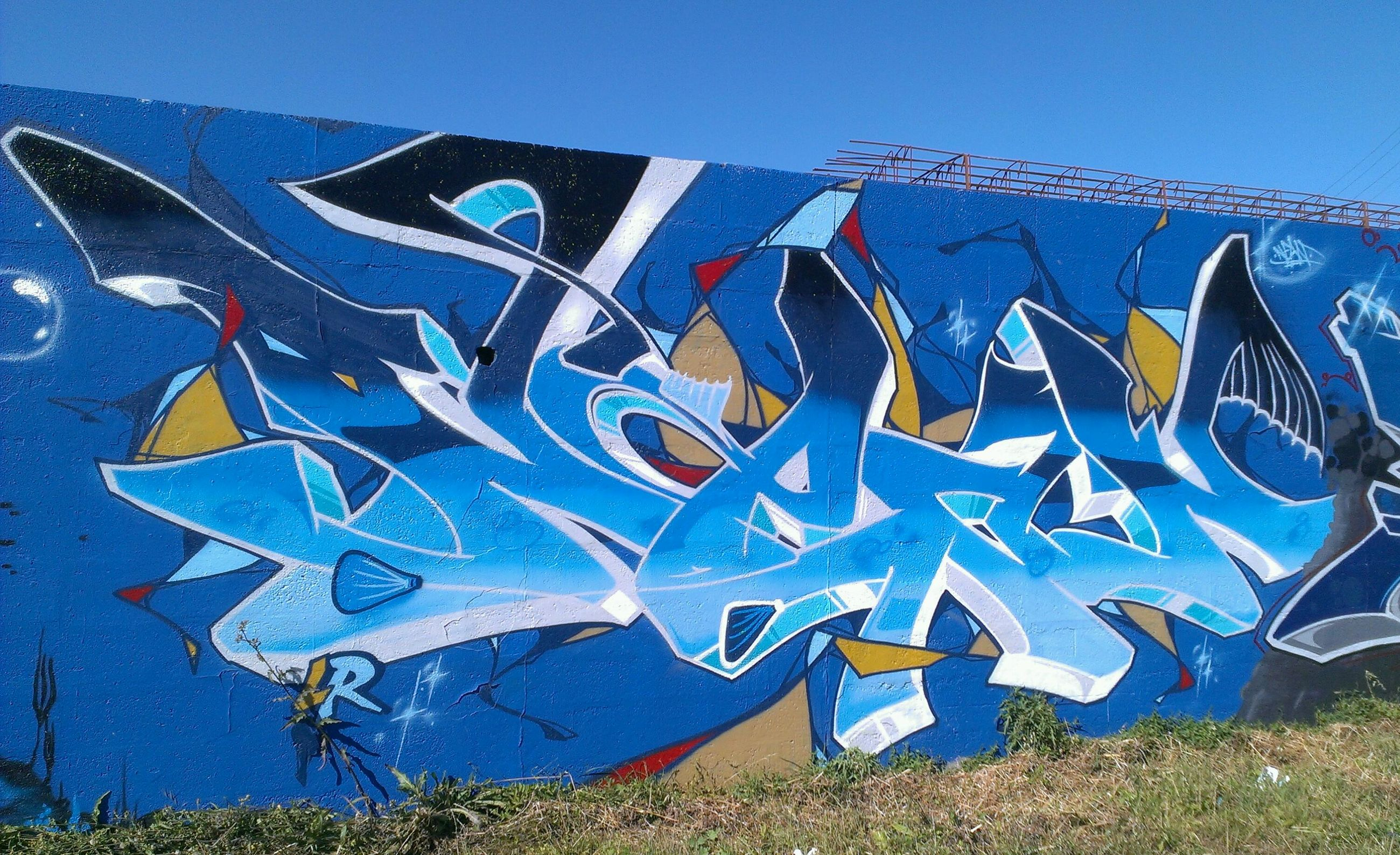 blue, graffiti, creativity, art, multi colored, western script, text, art and craft, clear sky, built structure, low angle view, communication, architecture, building exterior, day, wall - building feature, outdoors, no people, street art, sunlight