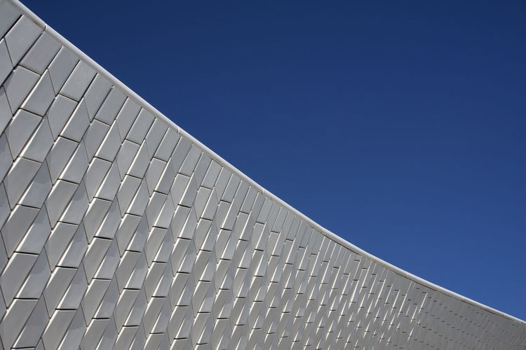 Tiled exterior of MAAT museum in Belem, Lisbon, Portugal under a clear blue sky Lisbon Portugal Belém White Tiles Abstract Sky Built Structure Blue Architecture Low Angle View Clear Sky Copy Space Sunlight Nature Building Exterior Day No People Pattern Modern Repetition Roof Building Outdoors Renewable Energy Environmental Conservation