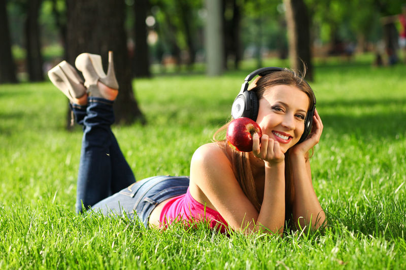 Woman with headphones listening music on the grass Beautiful Woman Outdoors Hairstyle Day Nature Women Teeth Toothy Smile One Person Cheerful Looking At Camera Leisure Activity Emotion Relaxation Portrait Lying On Front Young Adult Happiness Smiling Plant Lying Down Grass Real People Lifestyles Field Land Young Women