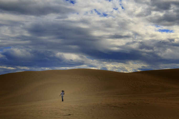 Man Walking On Desert Against Cloudy Sky
