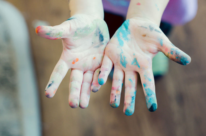Low section of child hand covered with powder paint