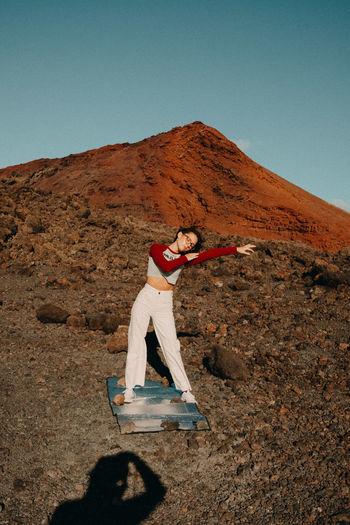 Man standing on arid landscape against clear blue sky