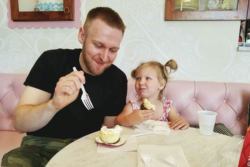 Two People Sitting Men Blond Hair Adult Table Indulgence Dessert Love Indoors  Cupcakes Daddy Daughter Time Dad Daughter Sharing  Admiration Adoring Child Children Photography Parent Loving Gaze