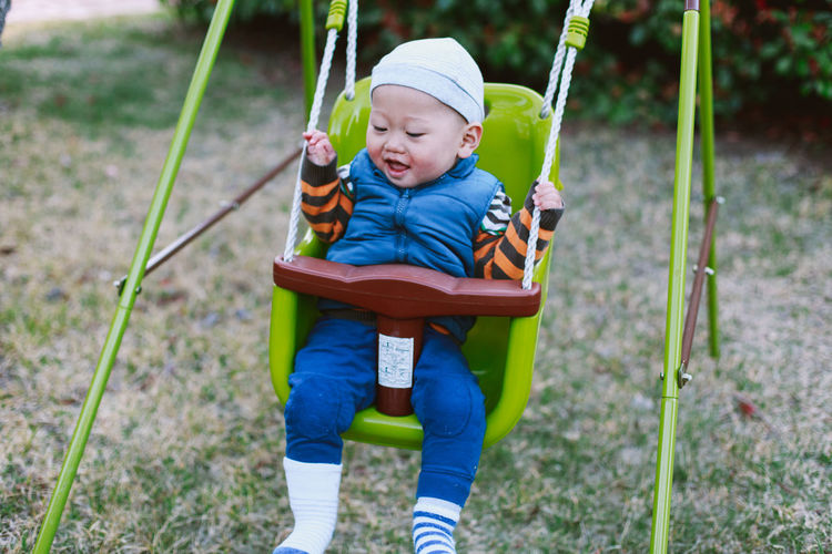 Cute baby boy sitting in swing at playground