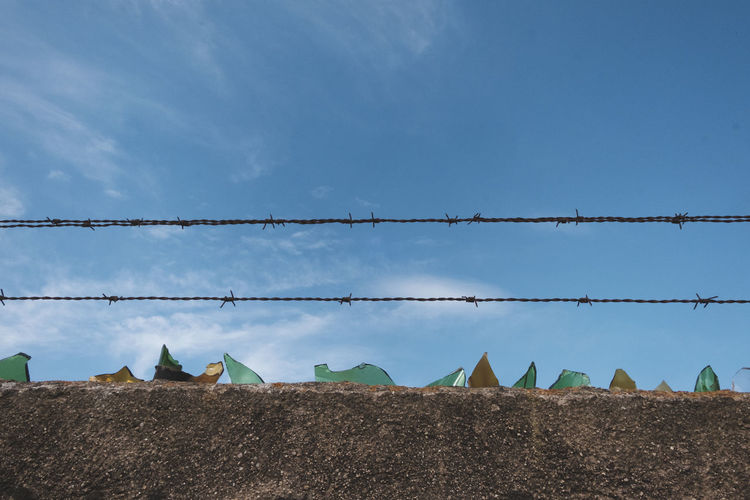 Low angle view of metal fence against blue sky