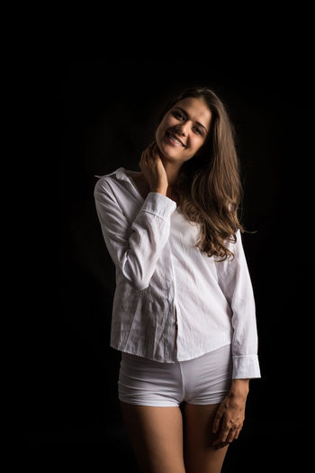 Portrait Black Background Studio Shot Long Hair One Person Looking At Camera Smiling Young Adult Hair Hairstyle Women Three Quarter Length Happiness Adult Standing Indoors  Beauty Beautiful Woman Front View Brown Hair Fashion Positive Emotion