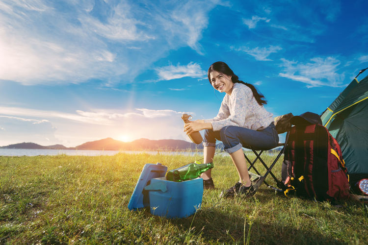 Portrait Of Smiling Young Woman Camping On Grassy Field Against Blue Sky
