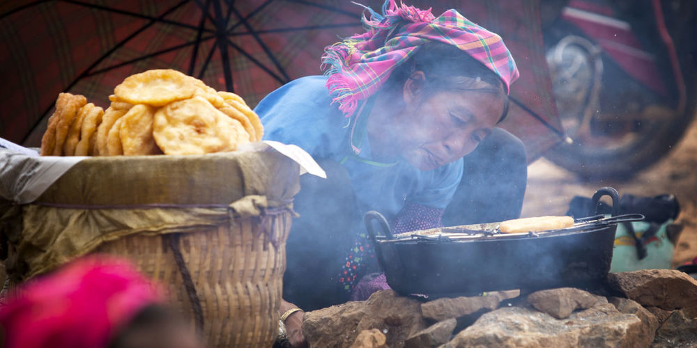 Woman preparing food on barbecue grill at market