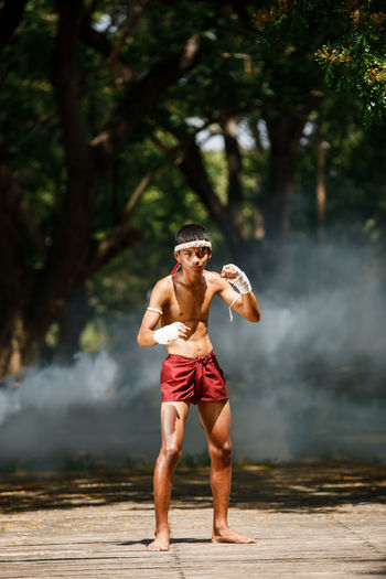 Full length of shirtless warrior standing in forest
