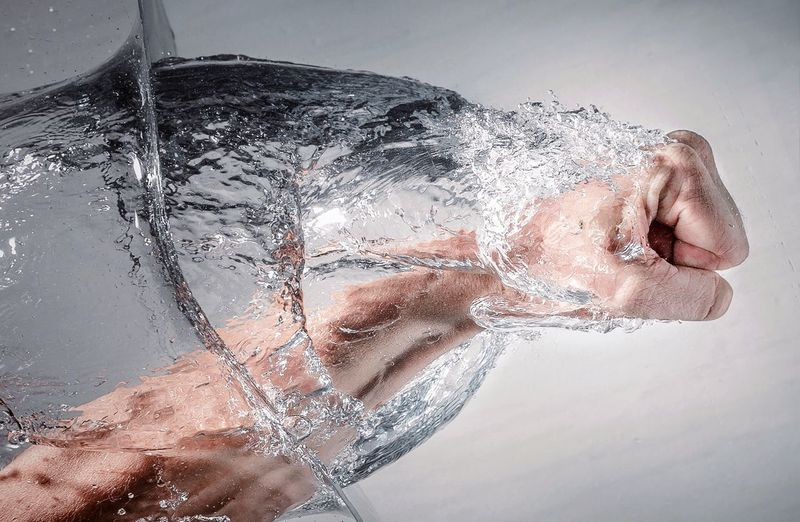 Digital Composite Image Of Man Punching Water Against Wall